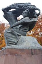 Frederic Chopin Statue Monument In Lazienki (Royal Baths) Park In Warsaw, Poland In Autumn With Foilage On The Trees