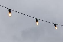 Light Bulb Garlands Against The Grey Sky