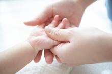 お母さんに手のベビーマッサージをしてもらう気持ち良い赤ちゃん