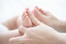 お母さんに足のベビーマッサージをしてもらう気持ち良い赤ちゃん