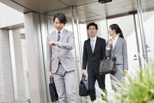 外出するビジネスマンと同僚