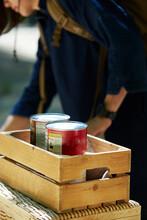 缶詰の入った木箱の奥で作業する女性
