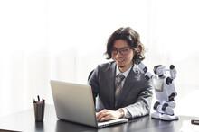 ロボットとパソコンを見るスーツを着た男性