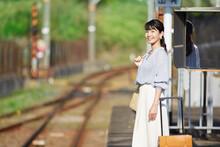 駅のホームで電車を待つ女性