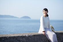 堤防に腰掛けている女性 ,日本,和歌山県,和歌山市,加太周辺