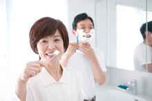洗面所で身支度をする中高年夫婦