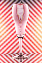 Refraction Of Light By A Tulip Champagne Glass On A Red And White Striped Background. Abstract Glass Art.