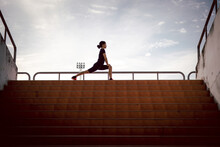 Running Woman Stretching During Morning Exercise On The Stadium Stairs Health Care Concept