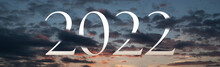 Symbolic New Years Eve Concept. Big 2022 Amongst The Evening Clouds With Sunset Light In The Background.