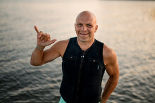 Smiling Bald Man In Vest Showing Surfer Gesture On The Water Background.