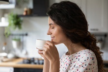 Happy Peaceful Woman Enjoying Morning Coffee In Kitchen, Holding Cup, Inhaling Aroma With Closed Eyes. Homeowner Relaxing Over Cup Of Hot Beverage At Home, Smiling, Thinking And Dreaming