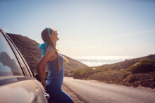 Woman On A Road Trip Arriving With Her Car By The Sea Enjoying Freedom