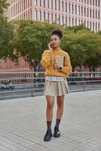 Vertical Shot Of Female Student Holds Notepads Makes Call Talks With Groupmate Wears Yelloow Knitted Jumper Skirt And Shoes Poses Outdoors Near Modern Building. Studying Technology Education