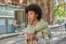 Outdoor Shot Of Pensive Curly Haired Young Woman Holds Mobile Phone Chats Online Tries To Find Way In Unknown City Wears Casual Outfit Browses Location Application During City Sightseeing Tour