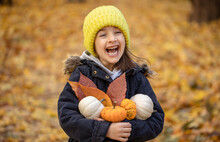 Little Funny Girl With Pumpkins In The Autumn Forest On A Blurred Background.