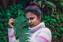 Young Indian Female In A Sweater Posing In A Forest With Ferns
