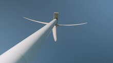 A Wind Turbine Spins On A Sunny Day. Low Angle Close Up Shot With Blue Sky