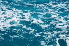 Water Surface Abstract Background. White Waves And Foam On The Blue Sea Water. Wake Behind Ship