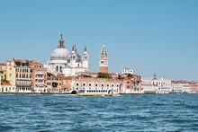 Old Buildings On Dorsodouro Promenade, Cupola Of Santa Maria Della Salute Church, St Mark's Campanile Tower In Venice, Italy. Traditional Venetian Architecture And Passenger Boat, View From Lagoon.