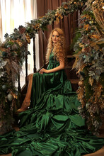 A Beautiful Blonde With Long Wavy Hair In A Chic Emerald Long Evening Dress Is Sitting On The Steps Of A Staircase Decorated With Christmas Toys