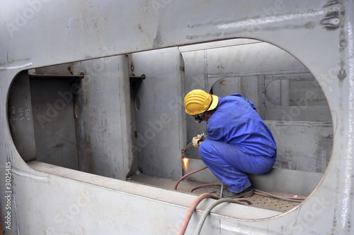 Welder with protective mask welding metal at Double bottom Cargo Ship Fototapet