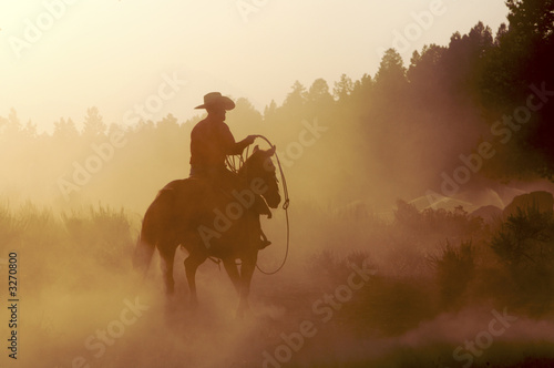 Fotografia Silhouette of cowboy riding horse at sunset