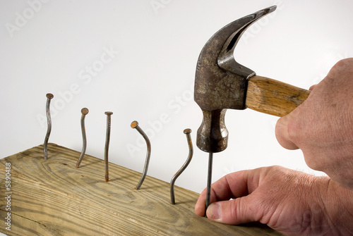 Hands holding hammer with bent nails exasperated Fototapet