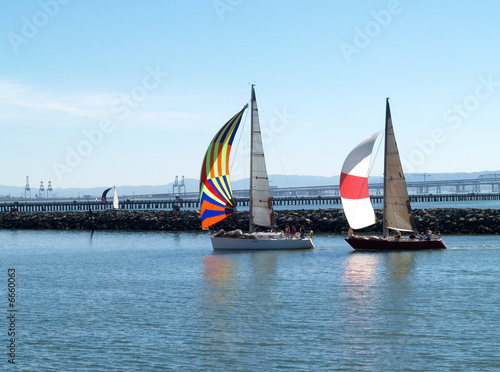 Cuadros en Lienzo Two Sailboats under Spinnakers running into port