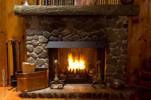 Photo close-up of stone fireplace in log cabin with blazing fire