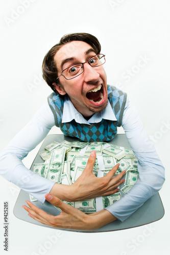 Portrait of greedy male raking in dollars and being glad Fototapeta