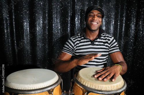 Fototapeta Portrait of young latino percusionist playing african drums