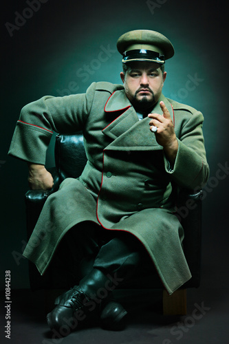 Leinwand Poster The evil dictator sitting in a chair