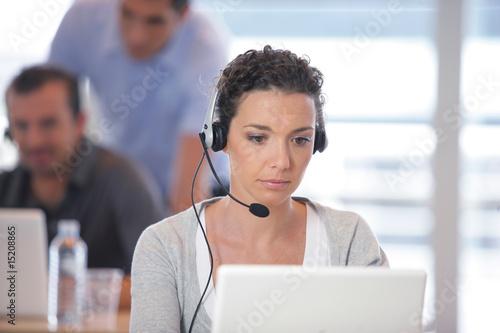 Obraz na plátně Femme assise devant un ordinateur portable avec un micro-casque
