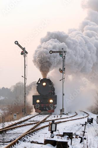 Fototapeta premium Retro pociąg parowy przechodzący przez wieś w okresie zimowym