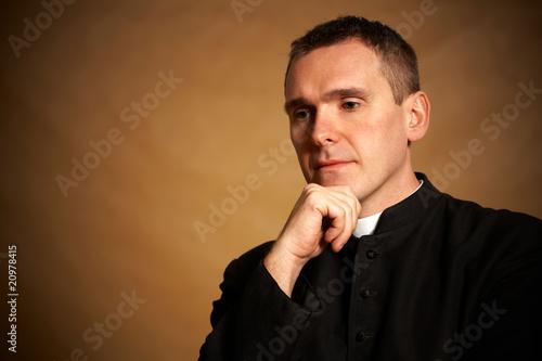 Obraz na płótnie Priest with hand under chin