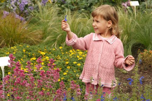 Obraz na płótnie girl holding in hand annual delphinium, pink around salvia