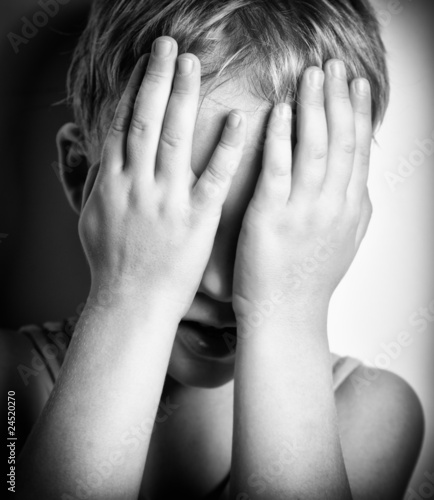 Canvas Print BW portrait of sad crying little boy covers his face with hands