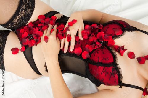Fototapeta Kobieta w bieliźnie z płatkami róż do pokoju