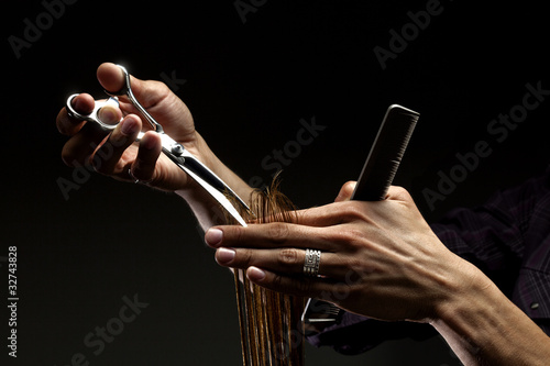 A close-up of hairdresser's hands cutting hair