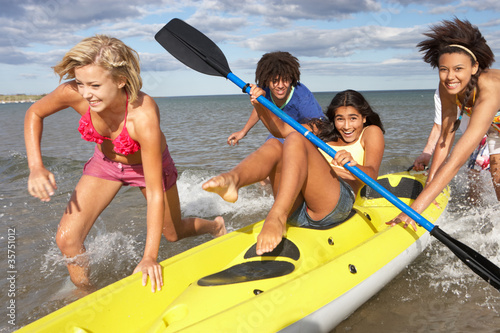 Teenagers in sea with canoe Poster Mural XXL