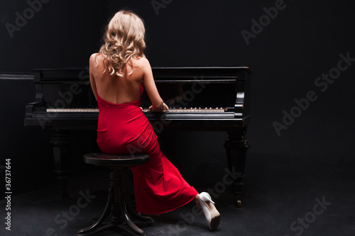 Canvas Print beautiful young attractive woman in cocktail dress and piano