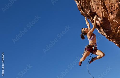 Slika na platnu Female climber clinging to a cliff.
