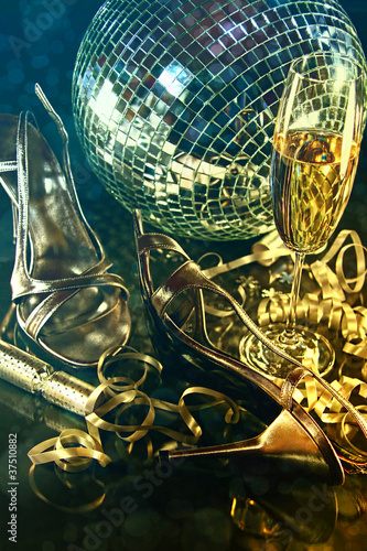 Silver party shoes on floor with champagne glass