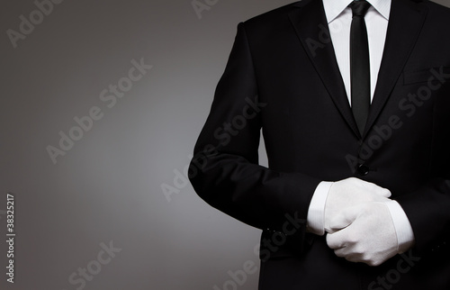 Fototapeta At Your service. Well dressed man waiting for orders with copy s