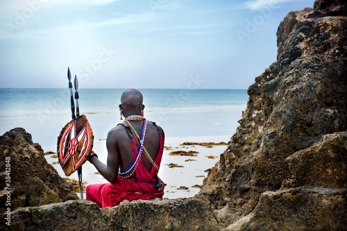 Wallpaper Mural Maasai sitting by the ocean on the beach