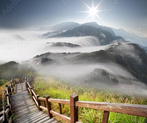 Naklejka premium Dramatyczne chmury z górą i drzewem