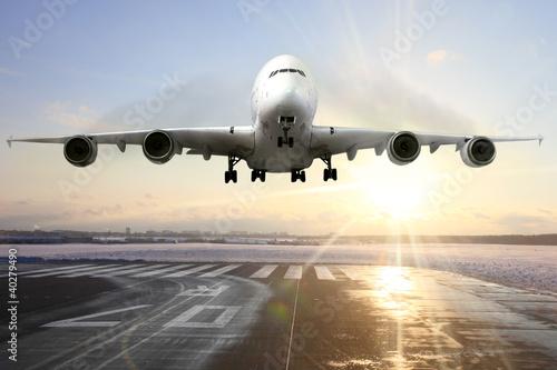Canvas Print Passenger airplane landing on runway in airport. Evening