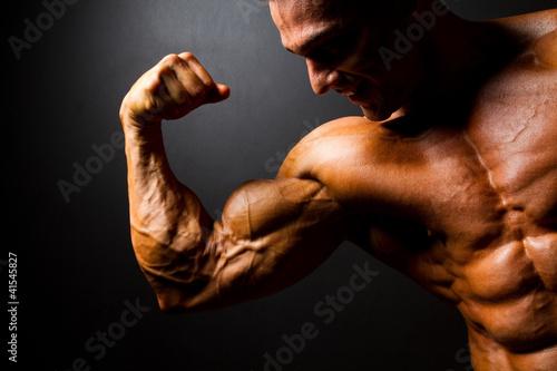 Wallpaper Mural strong bodybuilder posing on black background