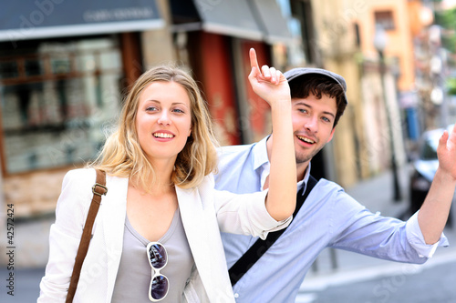 Foto Young couple hailing for a taxi cab