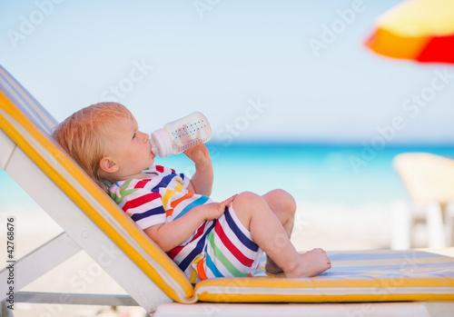 Fotografie, Tablou Portrait of baby on sunbed drinking water
